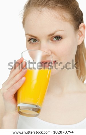 Woman drinking a glass of orange juice against white background - stock photo