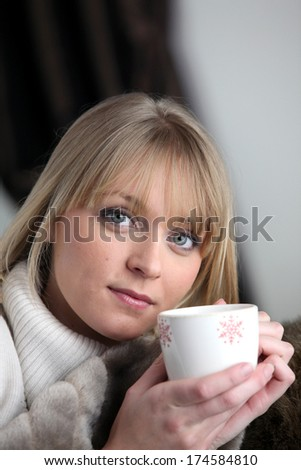 Woman drinking a hot drink - stock photo