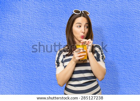 Woman drinking a juice with a red straw. Over blue background - stock photo