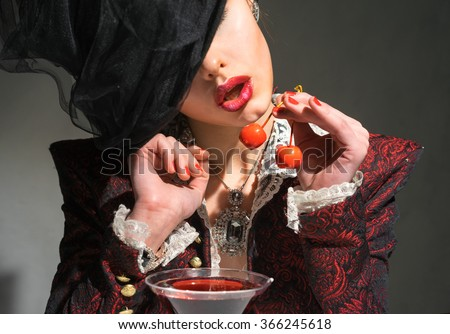 Woman drinking a martini with a cherry - stock photo