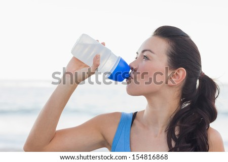 Woman drinking after exercising at beach - stock photo