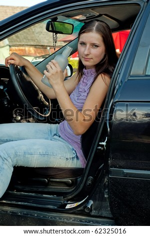 Woman drinking alcohol during a drive in a car - stock photo