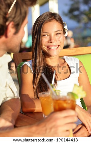 Woman drinking alcohol Mai Tai drink on Hawaii at beach club at sunset. Beautiful girl enjoying alcoholic beverage cocktail outside. Smiling happy mixed race Asian Caucasian woman on Hawaiian beach. - stock photo