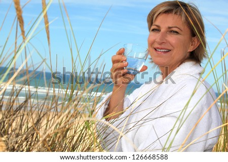 Woman drinking  by the seaside - stock photo