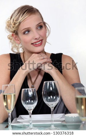 Woman drinking champagne at dinner - stock photo