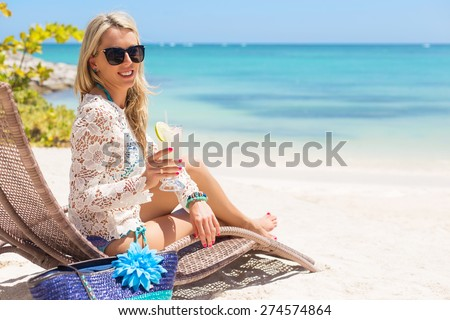 Woman drinking cocktail and relaxing in chair on the beach - stock photo
