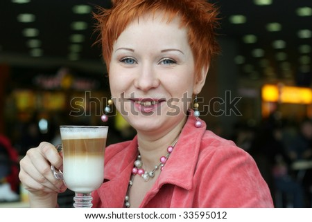 woman drinking coffe in cafe and smiling happy