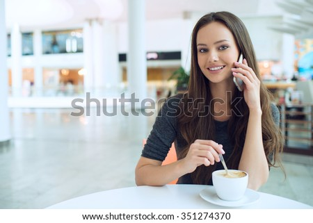 Woman drinking coffee and calling with cellphone. Portrait of the attractive girl in the restaurant - soft focus. Young happy lady enjoy breakfast