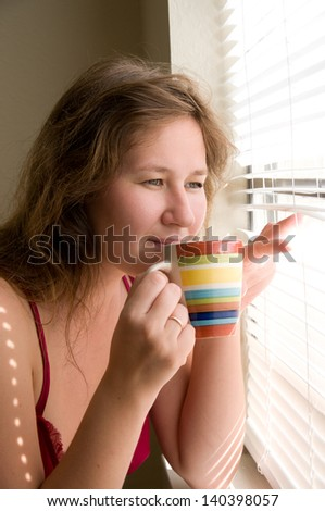 woman drinking coffee and looking through window