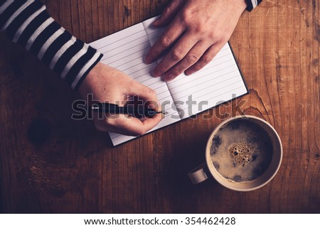 Woman drinking coffee and making a diary note, top view of female hands writing in notebook, retro toned image with selective focus. - stock photo