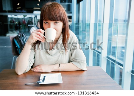 Woman drinking coffee at a corporate restaurant and looking at the camera - stock photo