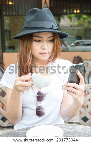 woman drinking coffee  at coffee shop and play mobile phone(soft - stock photo