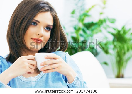 Woman drinking coffee at home. Beautiful girl portrait.