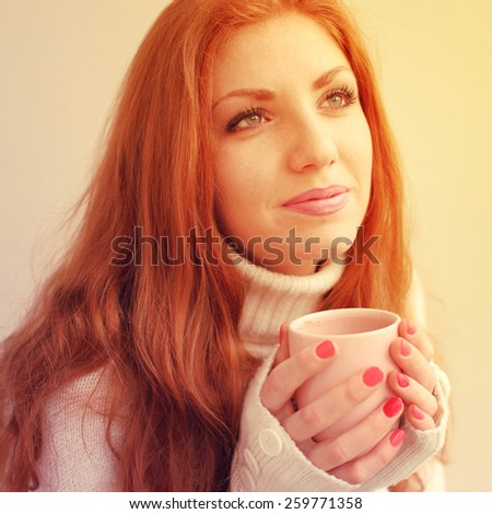 Woman drinking coffee at home with sunrise streaming in through window. Photo toned style Instagram filters - stock photo