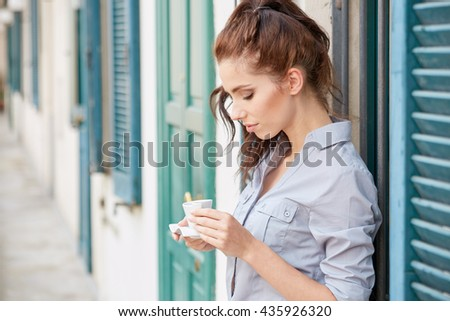 Woman drinking coffee at terrace on a sunny morning