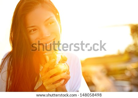 Woman drinking coffee in sunshine sitting outdoor in sun light enjoying her morning coffee. Smiling happy multiracial female Asian Chinese / Caucasian model in her 20s. - stock photo