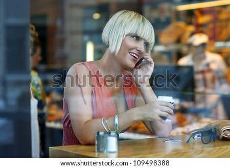 woman drinking coffee in the cafe window and talking to mobile phone - stock photo
