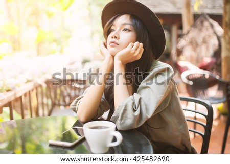 Woman drinking coffee in the garden, outdoor in sunlight light, enjoying her morning coffee. selective focus on face