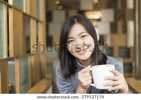Woman drinking coffee in the morning at cafe - stock photo