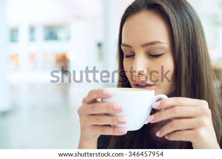 woman drinking coffee in the morning at restaurant soft focus. Closeup portrait of the pretty girl with cup of tea - stock photo
