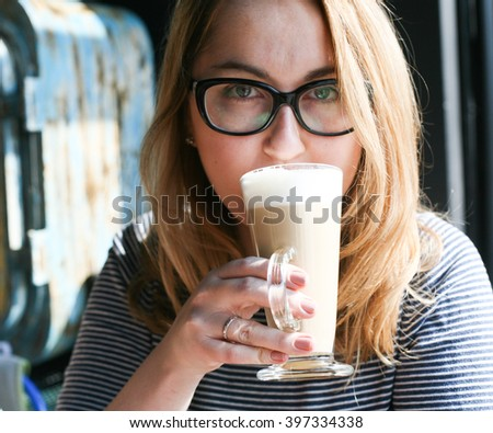 woman drinking coffee in the morning at restaurant (soft focus on eyes) - stock photo