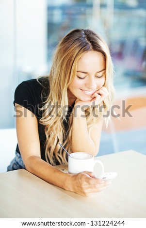 woman drinking coffee in the morning at restaurant (soft focus on the eyes) - stock photo