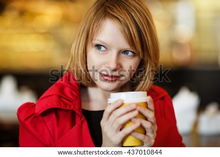 Woman drinking coffee indoors.