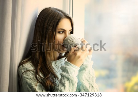 Woman drinking coffee near window in the room - stock photo