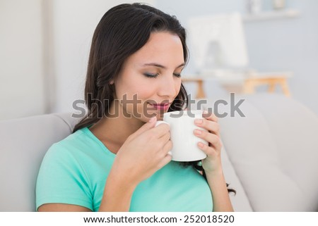 Woman drinking coffee on couch at home in the living room - stock photo