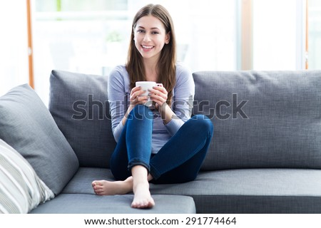 Woman drinking coffee on sofa  - stock photo