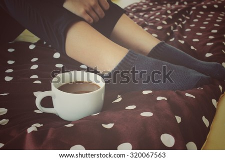 Woman drinking coffee on the bed