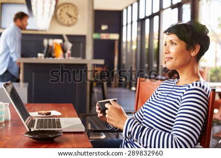 Woman drinking coffee, side view - stock photo