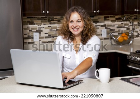 woman drinking coffee while working on ther laptop in the kitchen