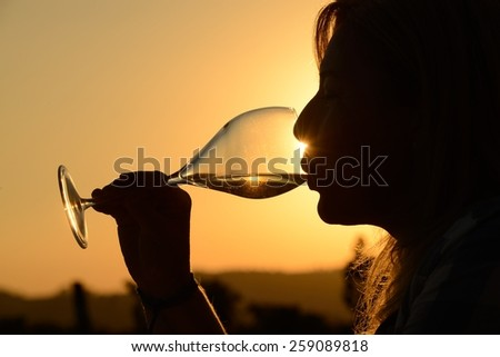 woman drinking glass of wine at sunset - stock photo