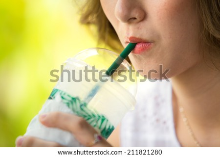Woman drinking iced coffee - stock photo