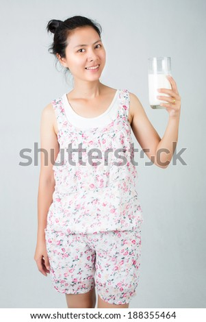 Woman drinking milk. Happy and smiling beautiful young woman enjoying a glass milk. - stock photo