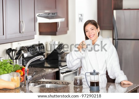 Woman drinking morning coffee in kitchen standing casual in bathrobe. Beautiful young mixed race Caucasian / Chinese Asian woman in her twenties. - stock photo