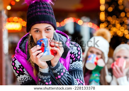 Woman drinking mulled wine in mug on German Christmas Market - stock photo
