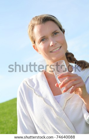 Woman drinking natural water in green field - stock photo