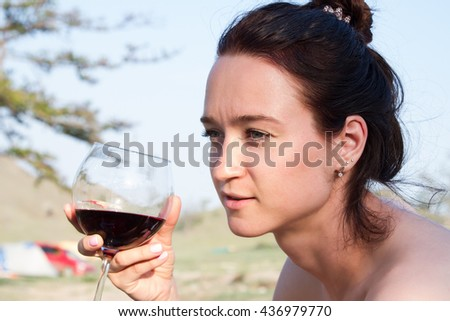 Woman drinking red wine at a picnic