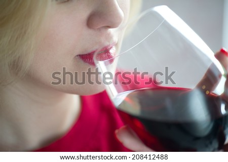 Woman drinking red wine with red lips - close portrait - stock photo