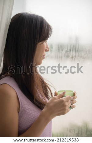 Woman drinking tea and looking out of the window on rainy day - stock photo