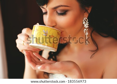 woman drinking tea from yellow cup