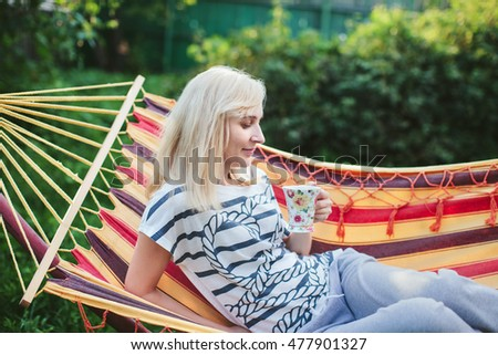 woman drinking tea while lying in a hammock