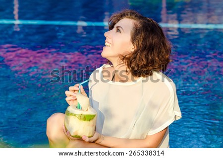 Woman drinking the coconut cocktail near the swimming pool - stock photo
