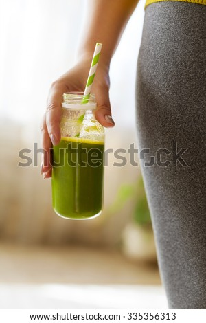 Woman drinking vegetable smoothie after fitness running workout. Fitness and healthy lifestyle concept