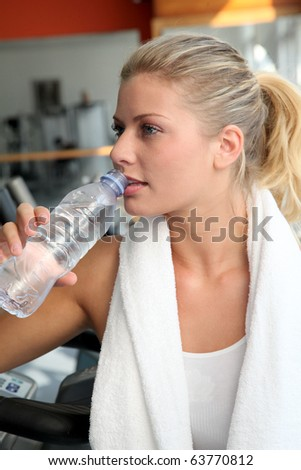 Woman drinking water after exercising - stock photo