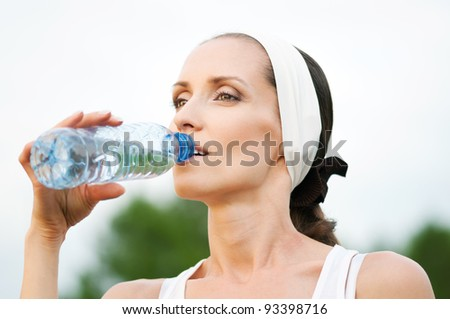 Woman drinking water at outdoors workout - stock photo