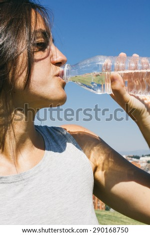 Woman drinking water during a training - stock photo