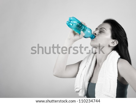 Woman drinking water from plastic bottle with eyes closed. - stock photo
